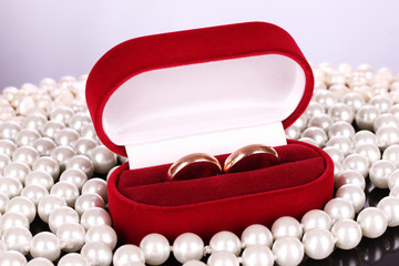 wedding rings in a box and pearls