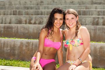 Pretty young blond and brunette women in a park setting