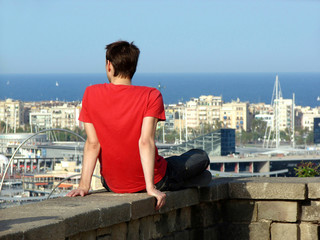 sitting young man looks at Barcelona