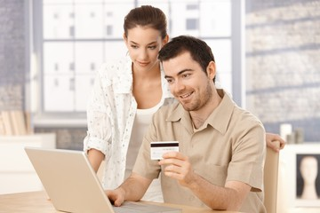 Happy couple shopping online at home smiling
