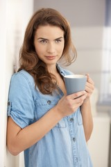 Attractive girl drinking tea at home