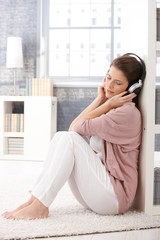 Woman on living room floor with headphone
