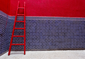 Colorful riad interior red ladder, blue tiled wall