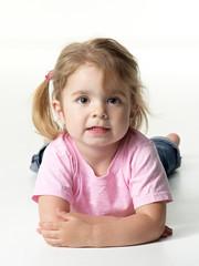 Portrait of adorable little girl lying on the floor