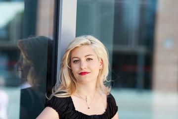 portrait einer jungen blonden frau in der stadt