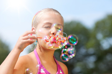 little girl blowing soap bubble outdoor
