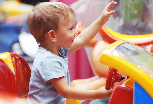 Cute Little Boy Riding a Toy Car