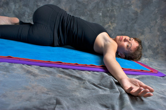 woman doing yoga posture Ardha Jathara Parivarttanasana or Half
