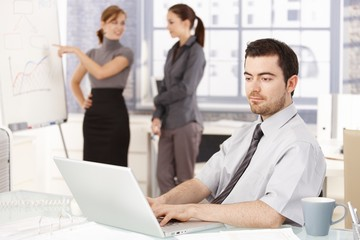 Businessman working in office women in background