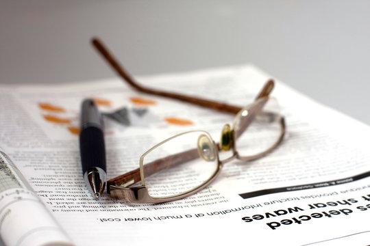 Pen, glasses and magazine