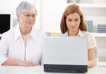 Beautiful woman and senior mother with laptop