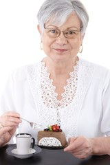 Portrait of senior woman with cake smiling