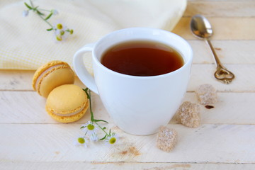 cup of fragrant tea with sugar and sweets