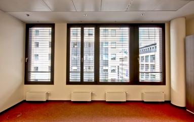 Büro mit Ausblick durch Jalousie auf Gebäude