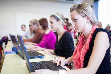 college students sitting in a classroom, using laptop computers