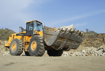 Front loader machine scooping up granite stones in a quarry