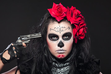 Young girl in day of the dead mask with gun