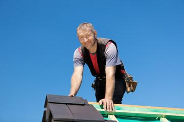 dachdecker legt dachpfannen