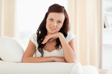 Young woman relaxing on a sofa looking into the camera