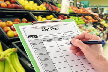 Hand with Pen Writing a Diet Plan by Supermarket Fruit