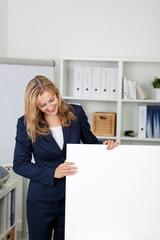 blonde frau im büro schaut auf weißes schild