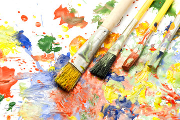 Four paintbrushes against a paint smeared background.