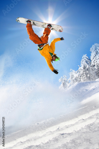 Wall mural Snowboarder jumping against blue sky