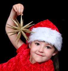 adorable girl in Christmas outfit playing with golden star ornam