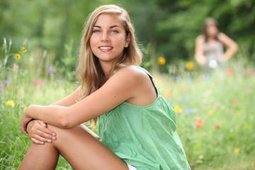Two female teenagers sat in field
