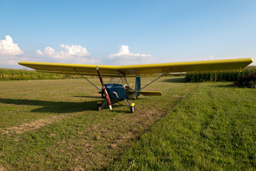 Small microlight aircarft parked in an airfield.