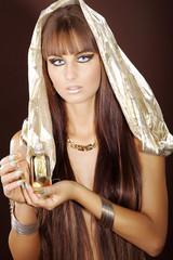 Wellness, hübsche Frau mit Kopftuch hält Massageöl in der Hand
