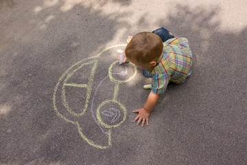 Boy drawing with chalk on the asphalt