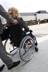 Female executive being pushed in wheelchair