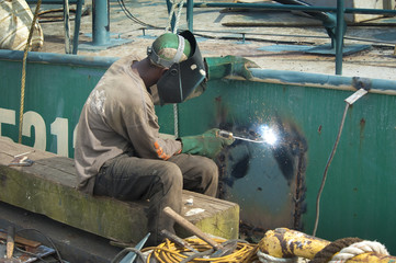 Welding a steel plate on the hull of a ship