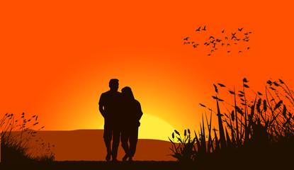 Loving couple against a sunset sky