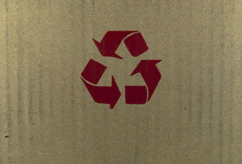 Red recycle symbol on cardboard.