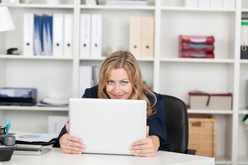 lächelnde frau blickt über ihren laptop