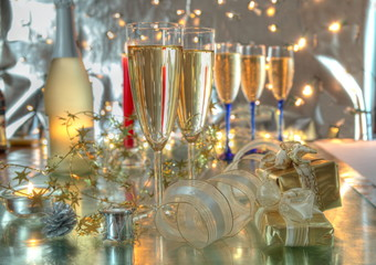 Champagne in glasses,gifts and lights on silver background.