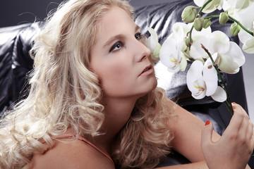 Hübsche blonde Frau riecht an Orchidee