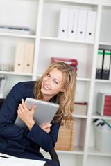 lachende blonde frau im büro mit ihrem laptop