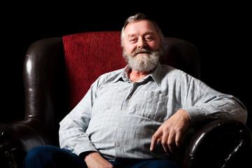 grinsender älterer Mann im Sessel sitzend