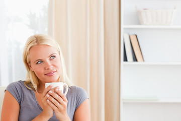 Woman sitting on a sofa with a cup of coffee