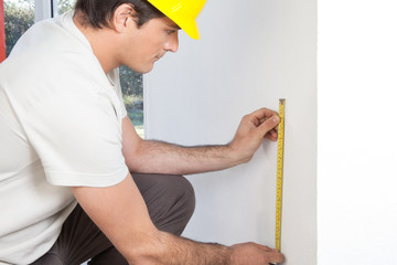 Young contractor measuring wall