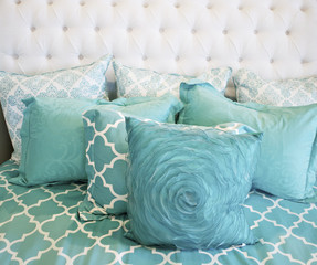 Teal colored cushions on bed