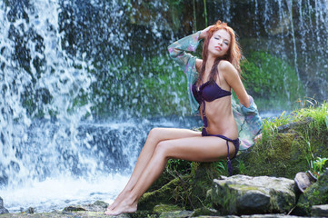 A young woman in purple lingerie on a waterfall background