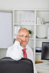 seriöser geschäftsmann stützt sich auf bürostuhl