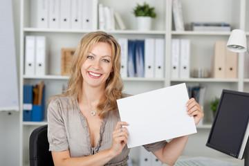 lächelnde blonde frau im büro zeigt weißes schild