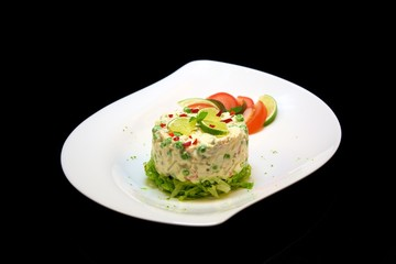 Chicken salad on black background in a fancy plate