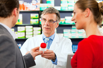 Pharmacist with customers in pharmacy