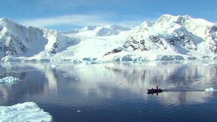 Wall Mural - small boat travels through antarctic ocean